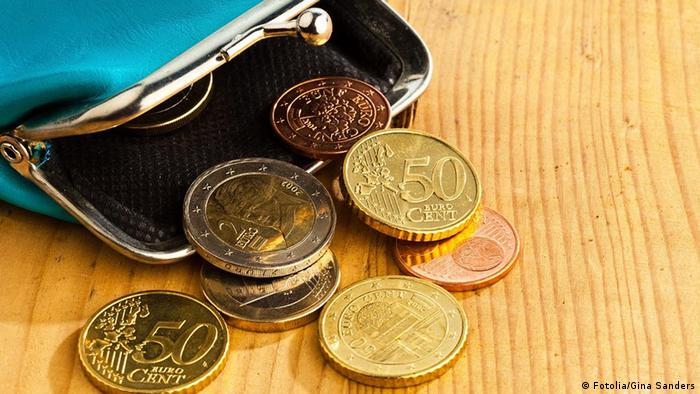 An empty, open coin purse with a few euro coins (various denomination) sticking out