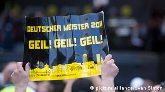 Ein Fan hält ein Pappschild hoch, auf dem steht: Deutscher Meister 2011, Geil! Geil! Geil!