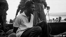 Deposed Congo Prime Minister Patrice Lumumba, hands manacled, sits in the bed of an army truck under guard of Congolese soldiers after his arrival at Leopoldville (Kinshasa) airport, Dec. 2, 1960, one day after his arrest by troops loyal to Col. Joseph Mobutu. Lumumba was executed the following month. This is believed to be one of the last photos of Lumumba alive. (AP Photo/Horst Faas)