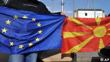 Two men bind E.U. And Macedonian flags in front of the Government building, in Macedonia's capital Skopje, celebrating the recommendation of European Commission to open accession talks with Macedonia, Wednesday, Oct. 14, 2009. The EU Enlargement Commissioner Olli Rehn, earlier Wednesday said the European Commission is recommending that the EU opens membership talks with Macedonia. (ddp images/AP Photo/Boris Grdanoski)
