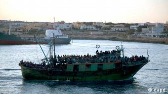 A boat carrying migrants enters Lampedusa's harbor, Italy, Friday, April 8, 2011. After days of fierce sparring, Italy and France patched up their differences Friday over the fate of thousands of Tunisian migrants, avoiding a major rift over European Union border control rules. Top security officials from Italy and France sought a conciliatory tone as they struggled with the crush of more than 20,000 Tunisians who sailed on often rickety boats to Italy's southernmost point, the tiny Mediterranean island of Lampedusa. (Foto:Giorgos Moutafis/AP/dapd) GREECE OUT