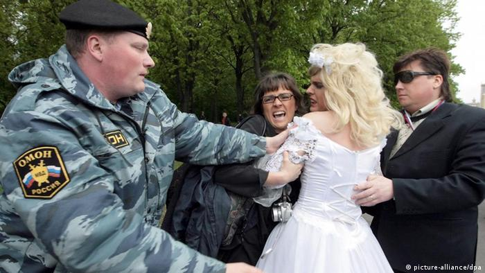 A Russian riot policeman detains a man dressed in bridal gown during an attempted rally of gay rights activists in Moscow, Russia, 16 May 2009. Moscow police violently broke up gay rights demonstrations, detaining more than 20 protesters who denounced what they called Russian homophobia hours before the finals of a major international pop music competition. EPA/ANDREI CHEPAKIN +++(c) dpa - Bildfunk+++