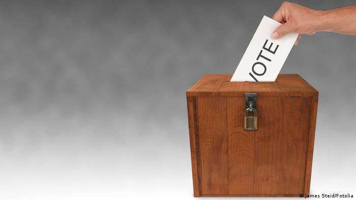 Hand placing ballot in wooden box