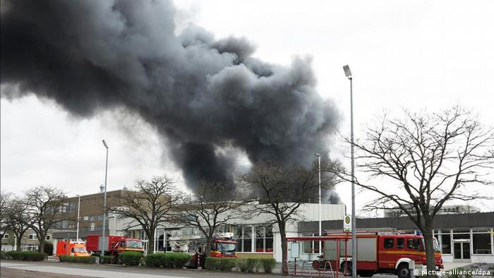 Black column of smoke rises over Marl. In the foreground, fire vehicles and trees