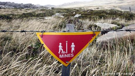 A sign with babed wire warning against landmines