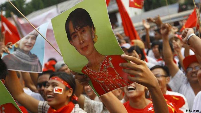 Supporters of the National League for Democracy (NLD) party cheer holding a portrait of Myanmar pro-democracy leader Aung San Suu Kyi