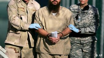 ** FILE ** A shackled detainee is transported on the grounds of Camp Delta detention center, Guantanamo Bay U.S. Naval Base, Cuba, in this Dec. 6, 2006 file photo, reviewed by a U.S. Dept of Defense official. Five years since the first detainees arrived here on Jan. 11, 2002, Guantanamo has in some ways changed, in some ways not. Open cages have been replaced by maximum-security buildings. The U.S. still holds nearly 400 men at its Navy base in southeast Cuba on suspicion of links to Al-Qaida or the Taliban, but has also released nearly as many. (AP Photo/Brennan Llinsley)