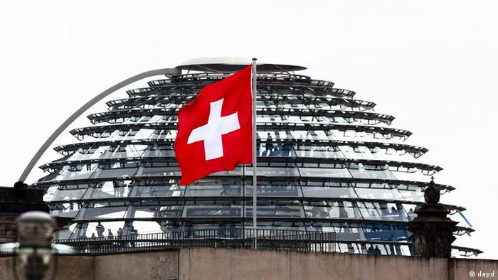 The Swiss national flag on top of Switzerland's embassy waves in the wind in front of the glass dome of the Reichstag building