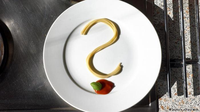 Zu einem Fragezeichen geformte Spaghetti liegen auf einem leeren Teller