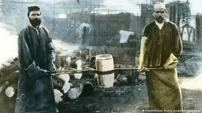 Foundrymen carry a melting pot with molten steel to the smelting furnace