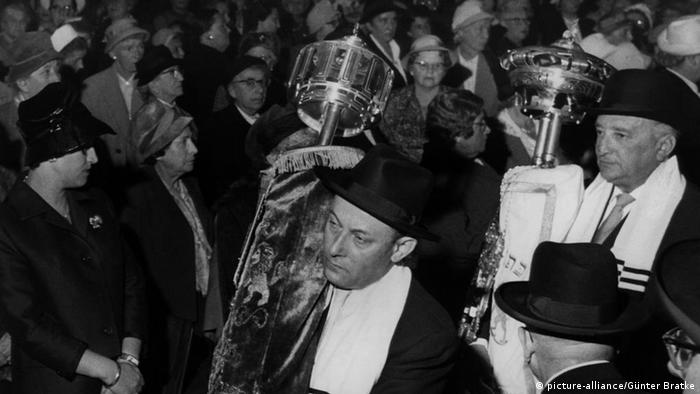 Heinz Galinski (center), head of the Berlin Jewish Community, carries a Torah scroll amid a crowd at a ceremony opening a the new Fasanenstrasse Synagogue in Berlin