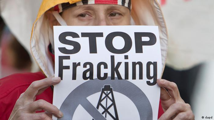 A woman covers her face with a sign that reads stop fracking (Photo:Vadim Ghirda/AP/dapd)