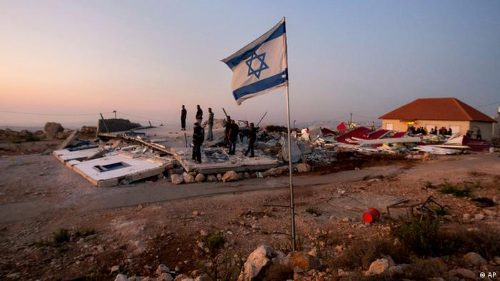 Jewish settlers stand on the rubble of a house demolished by the Israeli authorities in the West Bank settlement of Migron near the Palestinian city of Ramallah.