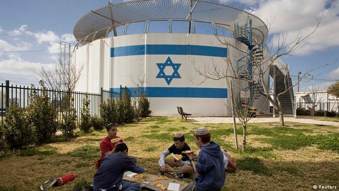 Israeli children eat pizza next to a water tank near the West Bank Jewish settlement of Beit El, near the West Bank city of Ramallah, Tuesday, March 1, 2011.