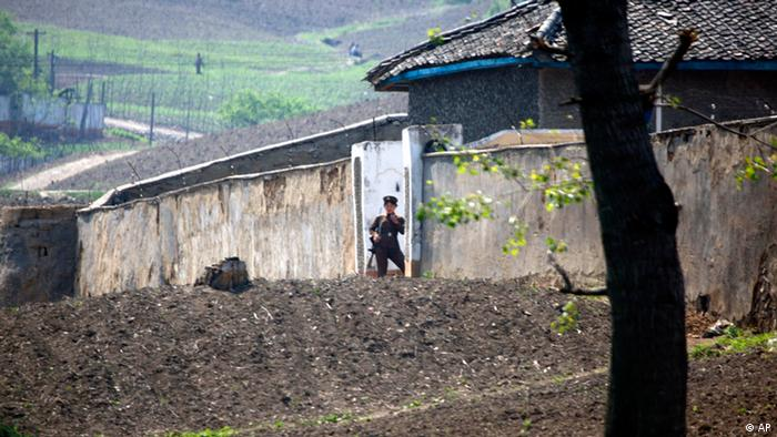 A North Korean soldier stands outside a prison for women along the North Korean river bank across from the Chinese border village of Hekou