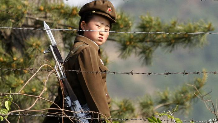 In this photo taken June 3, 2009, a female North Korean soldier looks out from behind a barbed-wire fence around a camp on the North Korean river banks across from Hekou, northeastern China's Liaoning province (ddp images/AP Photo/Ng Han Guan)