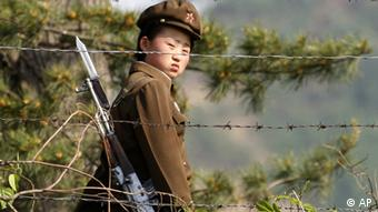 A female North Korean soldier looks out from behind a barbed-wire fence around a camp on the North Korean river banks across from Hekou, northeastern China's Liaoning province. North Korea's top court has convicted two U.S. journalists, and sentenced them to 12 years in labor prison, the country's state news agency reported Monday. (ddp images/AP Photo/Ng Han Guan)