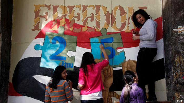 Art students from the University of Helwan decorate a wall