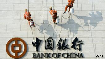 Chinese workers scale the wall near the logo for the Bank of China Ltd., China's second biggest commercial bank in Beijing, China. (Photo:ddp images/AP Photo/Ng Han Guan/DW)