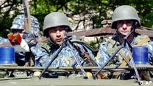 Uzbek special forces secure the area near a local Interior Ministry department in downtown Andijan, Tuesday, May 17, 2005. Security remained tight in Andijan on Tuesday after the worst unrest in Uzbekistan since it won independence in 1991, with armored vehicles guarding approaches to official buildings and troops in full combat gear watching out from behind concrete barricades. (AP Photo/Mikhail Metzel)