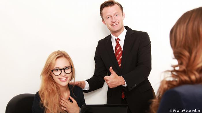 Девушка улыбается, стоящий рядом мужчина показывает большой палец в знак одобрения.