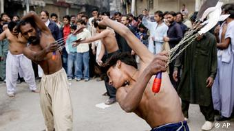 Pakistani Shiite Muslims flagellate themselves with knifes during a Muharram procession in Lahore, Pakistan