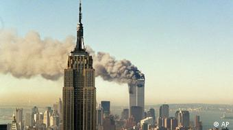 The twin towers of the World Trade Center burn behind the Empire State Building in New York, in this Sept. 11, 2001 file photo