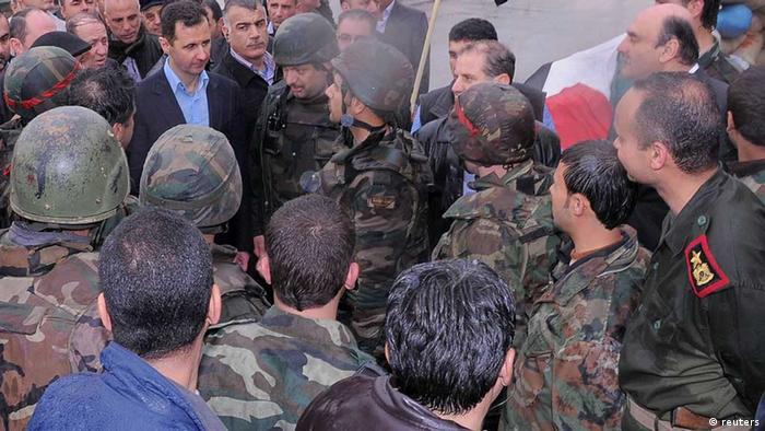 Syria's President Bashar al-Assad (C) meets soldiers during a tour in the Baba Amr neighbourhood of Homs in this handout photograph released by Syria's national news agency SANA on March 27, 2012. Assad visited the rebel stronghold in the city of Homs that his forces had overrun after weeks of shelling and gunfire, apparently to make the point that he can now tour the streets of the once bitterly fought-over district. REUTERS/SANA/Handout (SYRIA - Tags: POLITICS CIVIL UNREST MILITARY) FOR EDITORIAL USE ONLY. NOT FOR SALE FOR MARKETING OR ADVERTISING CAMPAIGNS. THIS IMAGE HAS BEEN SUPPLIED BY A THIRD PARTY. IT IS DISTRIBUTED, EXACTLY AS RECEIVED BY REUTERS, AS A SERVICE TO CLIENTS( eingest. sc)