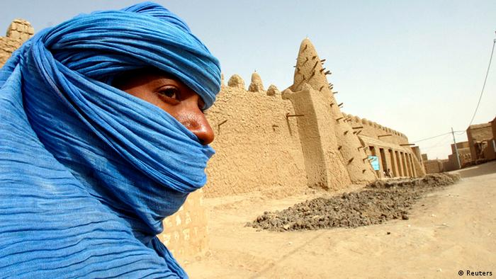 A Tuareg nomad stands near a 13th century mosque in Timbuktu in this March 19, 2004 file photo. Just as Timbuktu with its exotic staccato name is part of the lore of the Sahara, this same mystery cloaks the Tuaregs, those blue-robed desert marauders who have peopled adventure stories and Hollywood films for years. But there is nothing fictional about the rebels of the National Movement for the Liberation of Azawad (MNLA) who charged into Timbuktu on Sunday to plant their yellow, green, red and black flag in the city to claim it as part of a homeland covering an area of northern Mali the size of France. To match story MALI-TIMBUKTU/MYTH REUTERS/Luc Gnago/Files (MALI - Tags: POLITICS CIVIL UNREST RELIGION)