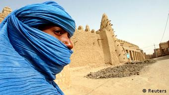 A Tuareg nomad stands near a mosque in Timbuktu