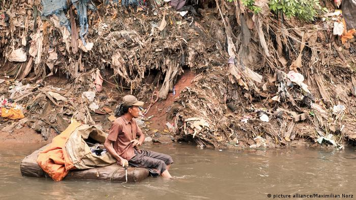 A man looks through garbage on a river in Jakarta (Photo: picture alliance / Maximilian Norz 14.02.2012)