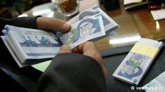 Eine Bankangestellte zählt Geldscheine im Iran (Foto: www.asio.ir)