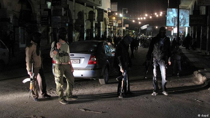 Free Syrian Army fighters guard a night protest in a neighborhood in Damascus