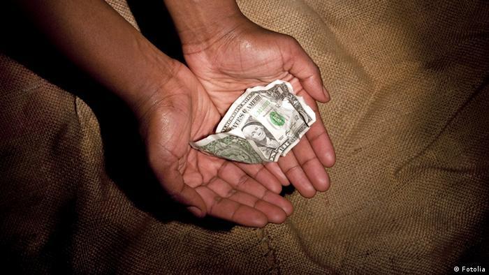 Eine Dollar-Note in zwei zu einer Schüssel geformten Händen symbolisieren das Thema Entwicklungshilfe. (© Andreas Wolf )