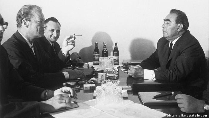 Black and white photo of a serious looking, smoking Willy Brandt and a smiling State Secretary Egon Bahr, principal negotiator with East Germany sitting across from Leonid I. Brezhnev