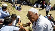 An elderly man wearing a traditional Muslim hat eats bread in a refugee camp in Kyrgyzstan, Tuesday, May 17, 2005. A group of 534 Uzbek refugees, including 96 women and 21 children, has managed to cross into Kyrgyzstan near the Uzbek village of Teshiktosh and set up a tent camp there. They received hot food and medical assistance arranged by the Kyrgyz authorities and the United Nations, and eight people were hospitalized with gunshot wounds. (AP Photo/Efrem Lukatsky)