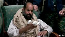 In this image taken from new video which has become available Tuesday Nov. 22, 2011, showing of Moammar Gadhafi's son Seif al-Islam examines his injured hand, in video taken shortly after his capture on Saturday Nov. 19, 2011, at a safe house in the town of Zintan, Libya. The video shows Seif al-Islam arguing with his captors and admonishing them saying that Libya's regions that were united in revolution will turn against each other in the near future and rip the country apart. Seif al-Islam says his hand was injured during a recent allied bombing. (Foto:APTN/AP/dapd) TV OUT