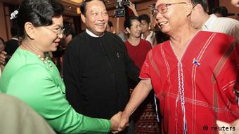 General Mutu Saipo (R) from the Karen National Union (KNU) and Myanmar's Minister of Immigration Khin Yee (C) and his wife shake hands during a welcome dinner ceremony at Sedona hotel in Yangon April 5, 2012. The ethnic armed group KNU delegation, comprising of General Secretary Naw Zipporah Sein, Military Affairs Committee Secretary Htoo Htoo Lay and KNLA GOC General Mutu Saipo, and the Myanmar government peace team comprising of Rail Transport Minister Aung Min and Immigration Minister Khin Yi met Yangon-based diplomats, INGO and journalists at a reception at the Sedona Hotel in Yangon today. The KNU delegation arrived here today to hold peace talks with the Myanmar government at Union Level on Friday. The two sides had earlier signed a ceasefire in Kayin State capital Pa-an in January. REUTERS/Soe Zeya Tun (MYANMAR - Tags: POLITICS) eingest. sc
