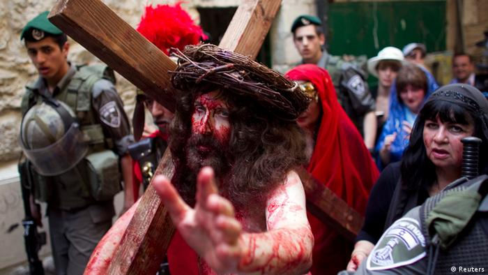 A man depicting Jesus holds a cross as he walks towards the Church of the Holy Sepulchre on Good Friday in Jerusalem's Old City April 6, 2012. Christian worshippers retraced the route Jesus took along Via Dolorosa to his crucifixion in the Church of the Holy Sepulchre. REUTERS/Darren Whiteside (JERUSALEM - Tags: RELIGION TPX IMAGES OF THE DAY)