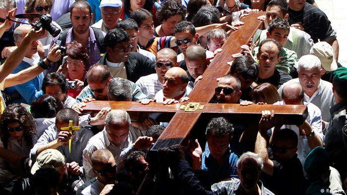 Arab Christian worshippers hold a cross as they take part in a procession on Good Friday in Jerusalem's Old City April 6, 2012. Christian worshippers retraced the route Jesus took along Via Dolorosa to his crucifixion in the Church of the Holy Sepulchre. REUTERS/Ammar Awad (JERUSALEM - Tags: RELIGION)