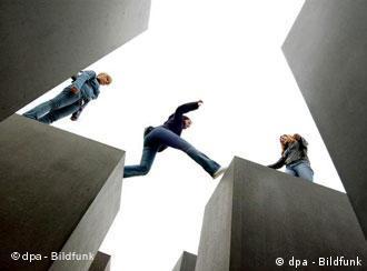 Zwei junge Frauen auf Betonpfeilern, eine dritte springt gerade von einem Pfeiler zum anderen