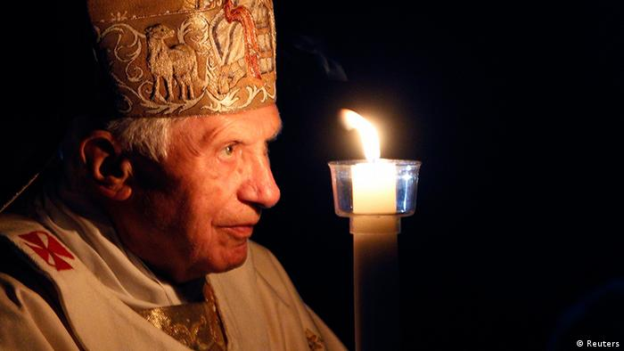 Pope Benedict XVI prays while holding a candle light as he arrives to lead a vigil mass during Easter celebrations at St. Peter's Basilica in the Vatican April 7, 2012. REUTERS/Alessandro Bianchi (VATICAN - Tags: RELIGION)