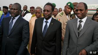 Traore, center, Mali's parliamentary head who was forced into exile after last month's coup, walks with Burkina Faso's Foreign Affairs Minister Djibrill Bassole, right, as Traore arrives at the airport to take up his constitutionally-mandated post as interim president, in Bamako, Mali Saturday, April 7, 2012.