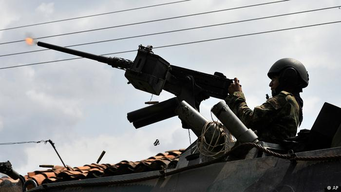 A solider fires a machine toward rebel positions in Caloto, southern Colombia