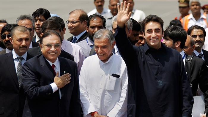 Pakistan President Asif Ali Zardari, front left, and his son Bilawal Bhutto Zardari, front right, gesture as India's Parliamentary Affairs Minister Pawan Kumar Bansal greets them after their arrival at the Palam Airfield in New Delhi, India, Sunday, April 8, 2012. Zardari arrived in India on a private trip Sunday that also gives him a chance to meet Indian leaders amid a thaw in relations between the two South Asian rivals. (AP Photo/Saurabh Das)