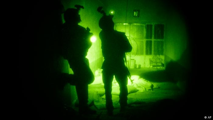 FILE - In this Oct. 28, 2009 file photo taken with a night vision scope, U.S. Special Operations forces search a home during a joint operation with Afghan National Army soldiers targeting insurgents operating in Afghanistan's Farah province. Increased nighttime military raids by international military forces in Afghanistan have created a resentment that has undercut any battlefield gains from the tactic, according to a report released Monday, Sept. 19, 2011, by a U.S. think tank. (AP Photo/Maya Alleruzzo, File)