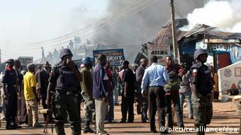 Nigerian police control a street shortly after a bomb blast
