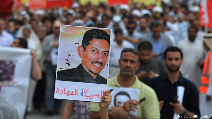 A protester holding a placard with the picture of rights activist Abdulhadi al-Khawaja and the words 'freedom or martyrdom' written in Arabic