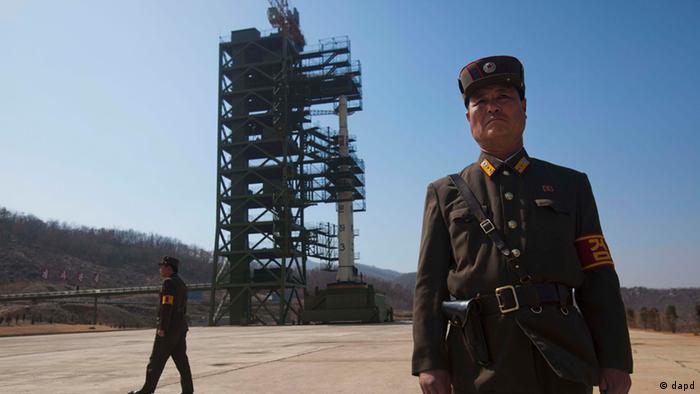 North Korean soldiers stands in front of the country's Unha-3 rocket, slated for liftoff between April 12-16, at Sohae Satellite Station in Tongchang-ri, North Korea on Sunday April 8, 2012. North Korean space officials have moved a long-range rocket into position for this week's controversial satellite launch, vowing Sunday to push ahead with their plans in defiance of international warnings against violating a ban on missile activity. (Foto:David Guttenfelder/AP/dapd)