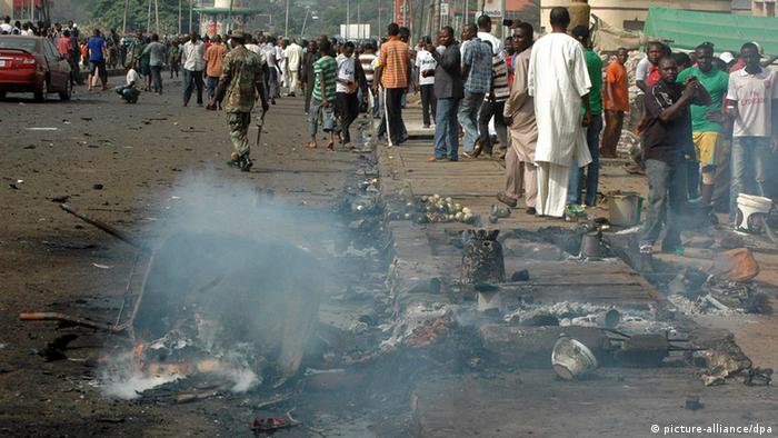 Nigerians look on at the damage after a suicide bomber detonated a car bomb in Kaduna, Nigeria